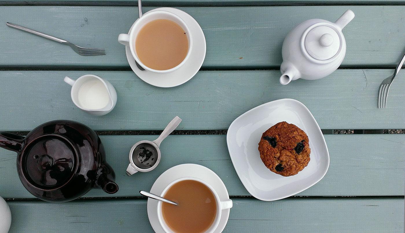 mesa de madera azul con el te y una magdalena servido