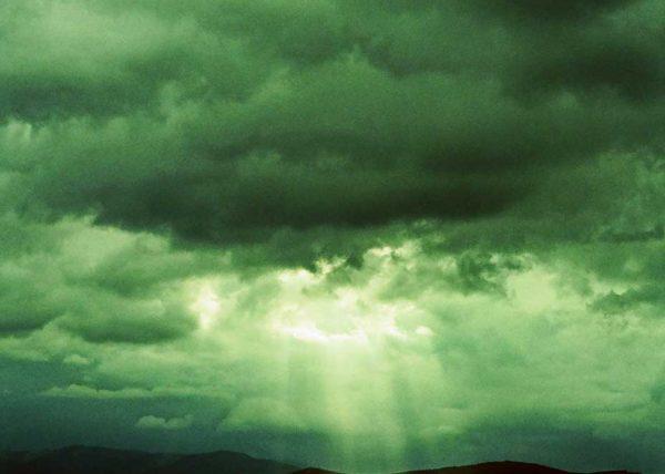 Rayo de luz sale entre las nubes con la montaña en silueta