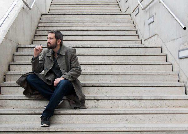 Retrato hombre fumando sentado en escalera
