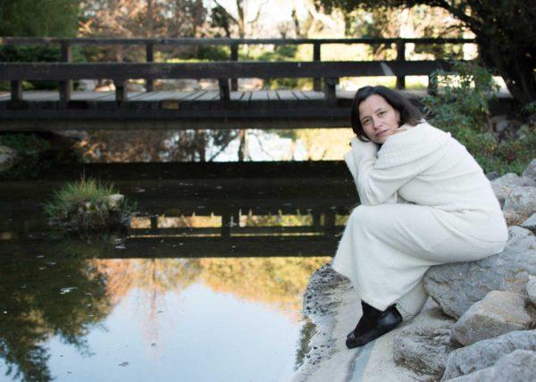 Mujer sentada junto a un estanque