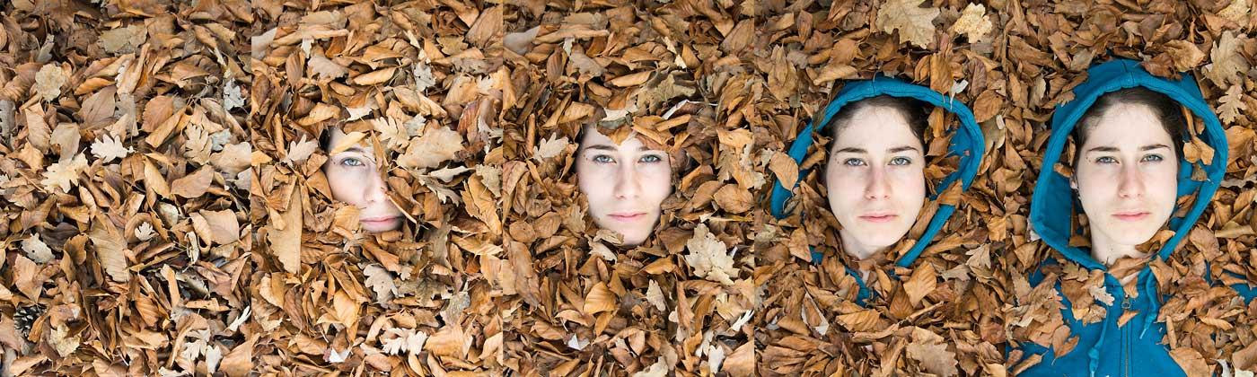 Chica cubierta por un lecho de hojas. Las hojas van desapareciendo y va apareciendo su cara.